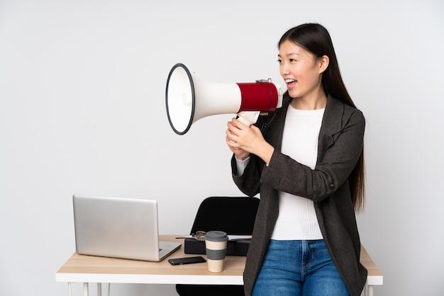 Бизнес азиатская женщина на ее рабочем месте, изолированных на белом фоне, крича через мегафон