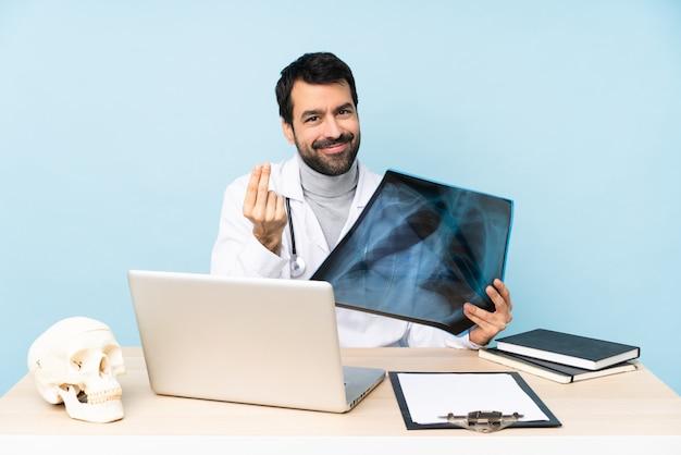 Профессиональный травматолог на рабочем месте, делая деньги жест