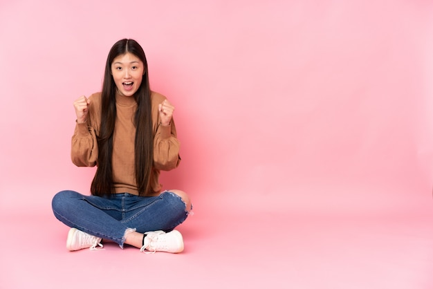 勝者の位置で勝利を祝っているピンクのスペースに分離された床に座っている若いアジア女性