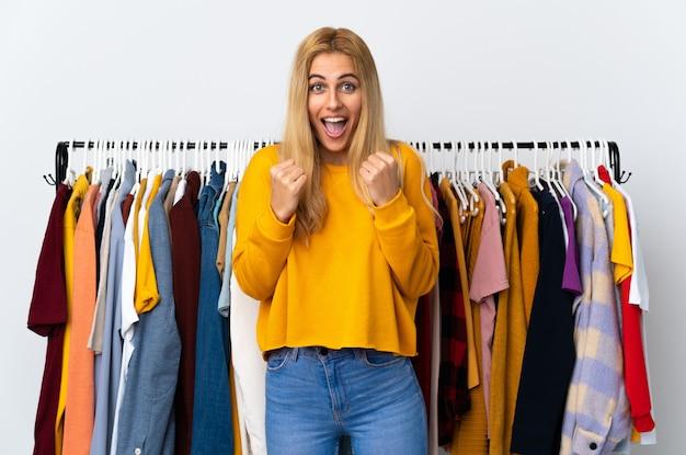 勝者の位置で勝利を祝っている衣料品店の若いブロンドの女性