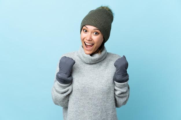 Молодая уругвайская девушка в зимней шапке на синем фоне празднует победу