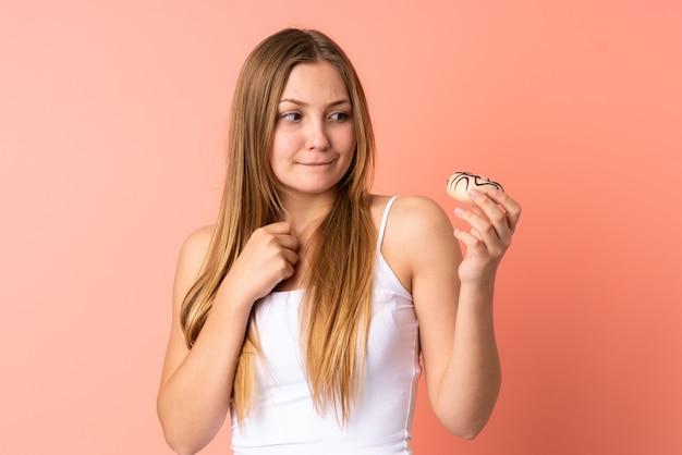 ドーナツを持ってピンクに分離されたティーンエイジャーのウクライナの女の子