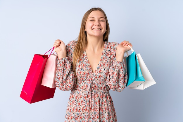 買い物袋を押しながら笑みを浮かべて青に分離されたティーンエイジャーのウクライナの女の子