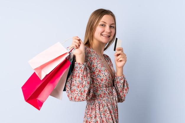 ショッピングバッグとクレジットカードを保持している青に分離されたティーンエイジャーのウクライナの女の子