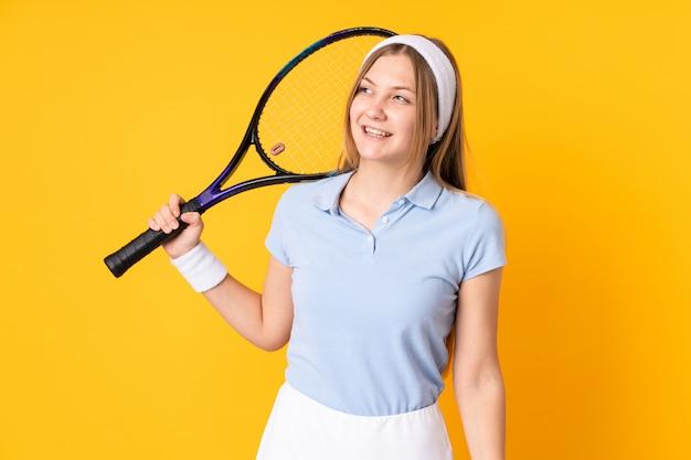 Украинский теннисистка подростка изолированная на желтом цвете играя теннис и смотря вверх