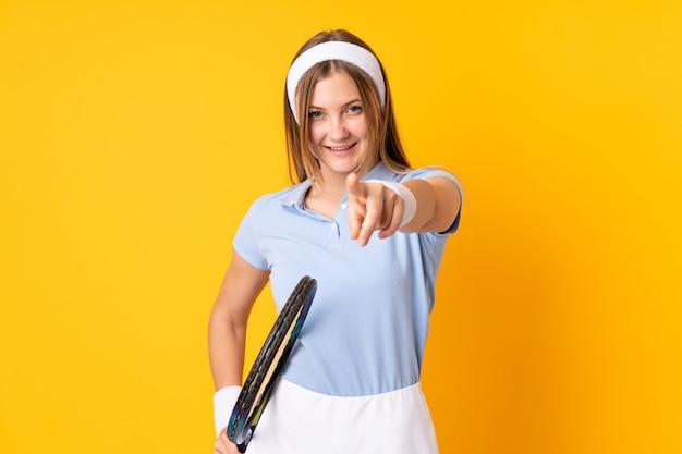 Подросток украинская девушка теннисистка, изолированных на желтом, играя в теннис и указывая на фронт