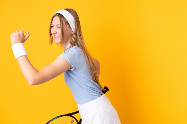 Украинская теннисистка подростка изолировала на желтом цвете играя теннис и празднуя победу