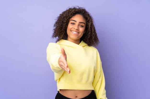 Молодая афроамериканская женщина, изолированная на рукопожатии для закрытия хорошей сделки