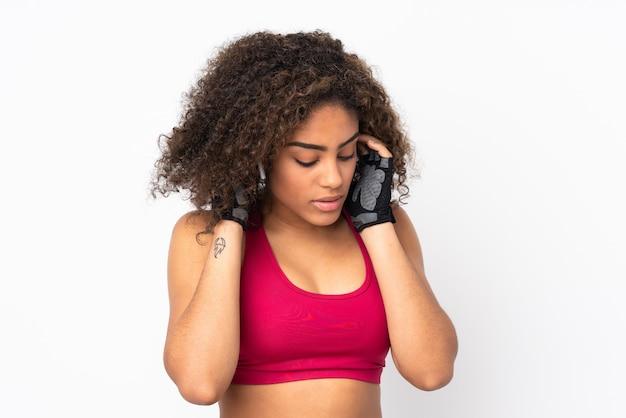 Молодая афро-американская женщина спорта изолированная на белой слушая музыке