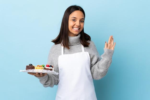 幸せな表情で手で敬礼分離ブルーに大きなケーキを持ってパティシエ