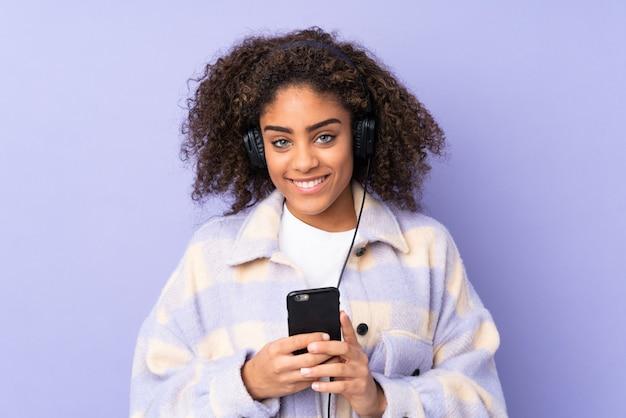 Молодая афро-американская женщина изолированная на фиолетовой слушая музыке с чернью и смотрящ перед