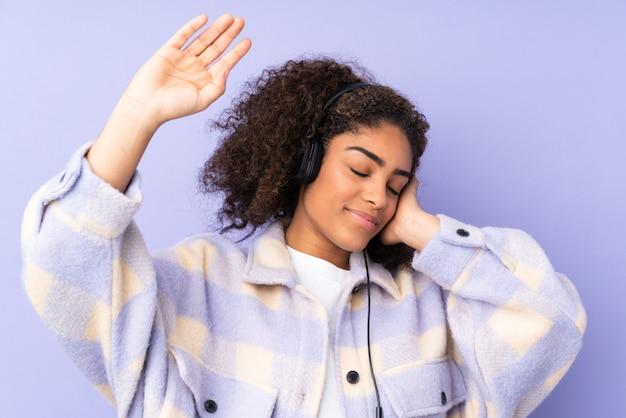 Молодая афро-американская женщина изолированная на фиолетовой слушая музыке и танцах