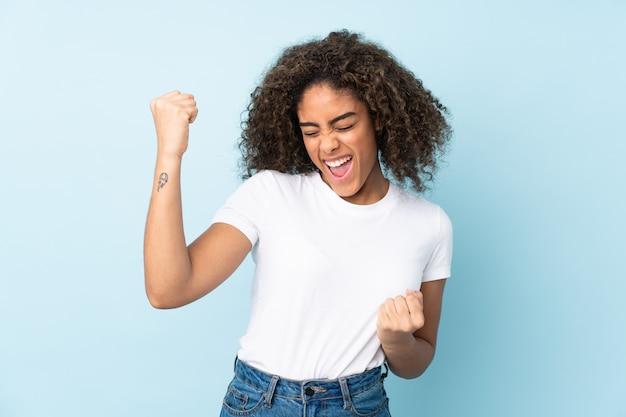 Молодая афро-американская женщина изолированная на сини празднуя победу