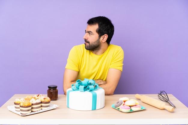 Человек в таблице с большим портретом торта