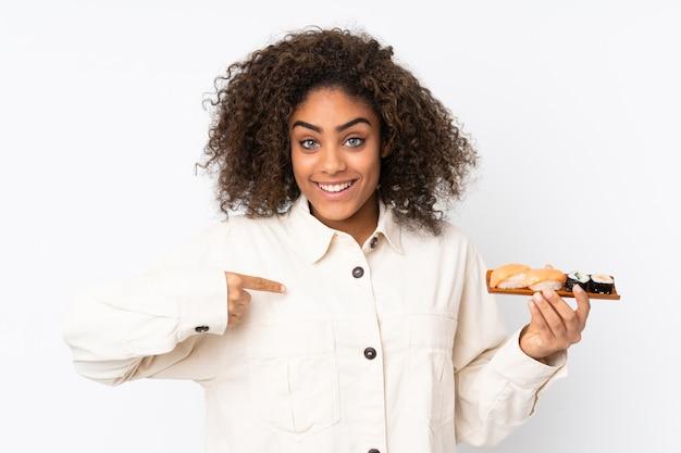 驚きの表情で白で隔離される寿司を保持している若いアフリカ系アメリカ人女性