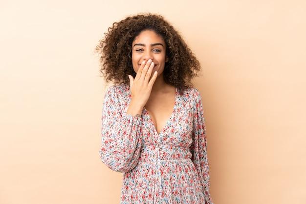 幸せなベージュと笑顔の手で口を覆っているベージュに分離された若いアフリカ系アメリカ人女性