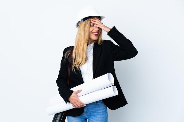 Молодая женщина архитектора с шлемом и держать чертежи на изолированном белом смеяться над
