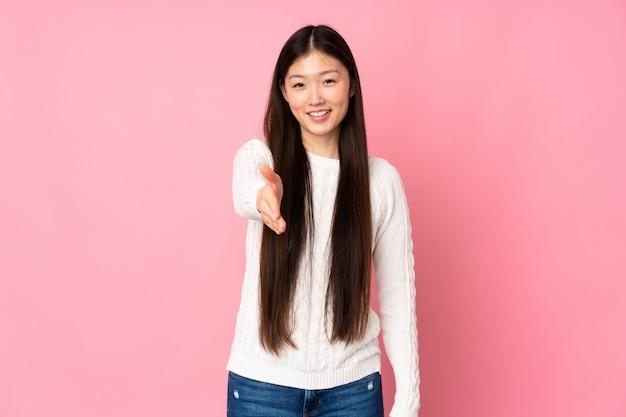 Молодая азиатская женщина на изолированном рукопожатии для закрытия хорошей сделки