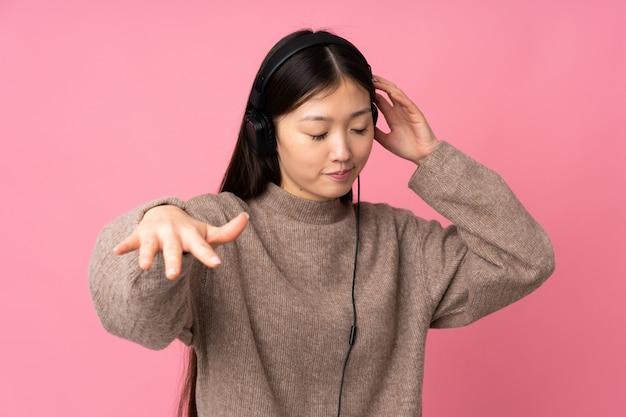 ピンクのリスニング音楽とダンスに分離された若いアジア女性