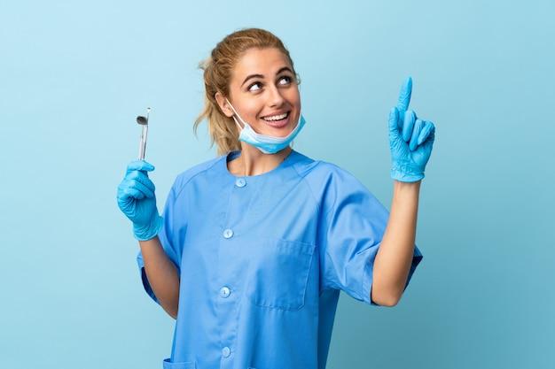 人差し指で素晴らしい分離を指している孤立した青いツールを保持している若い女性歯科医素晴らしいアイデア