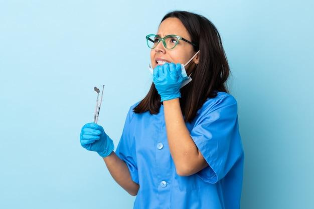 孤立した壁の上にツールを保持している若いブルネットの混血歯医者女性は少し緊張しています