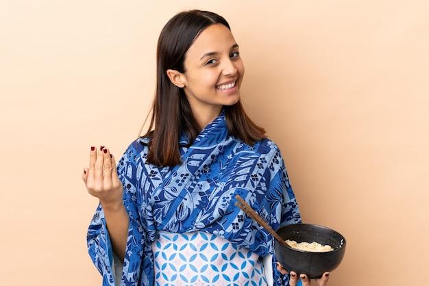 Женщина носить кимоно и проведение миску с лапшой, приглашая прийти с рукой. рад, что вы пришли, держа миску лапши с палочками для еды