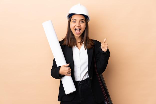Молодая женщина архитектор держит чертежи над изолированной стеной, показывая знак ок и большой палец вверх жест