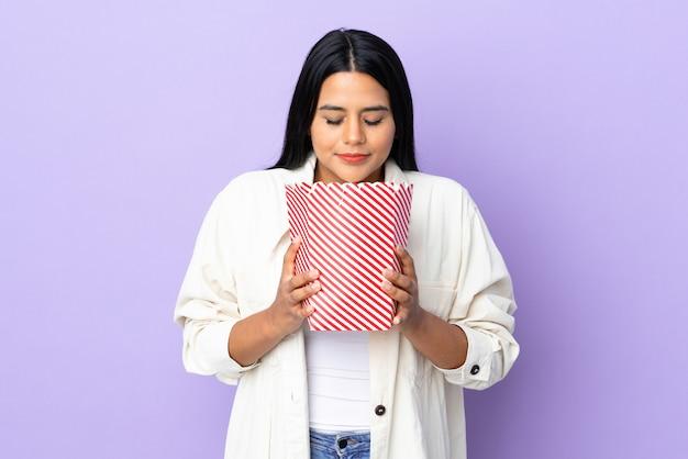 ポップコーンの大きなバケツを保持している白い壁に分離された若いラテン女性