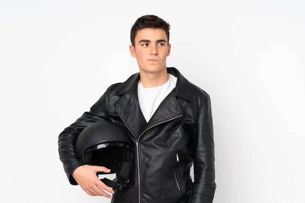 アイデアを考えて白い壁に分離されたオートバイのヘルメットを抱きかかえた