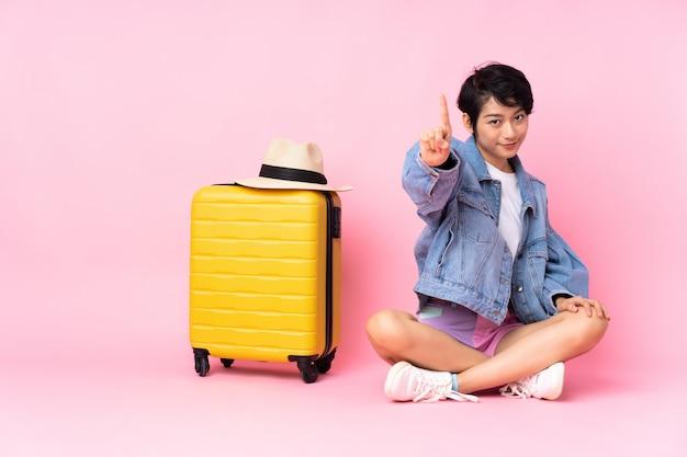 孤立したピンクの壁を示すと指を持ち上げて床に座っているスーツケースを持つ若い旅行者ベトナム女性