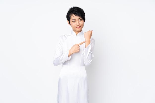 Молодая вьетнамская женщина с короткими волосами в традиционном платье на белом фоне, делая жест опоздания