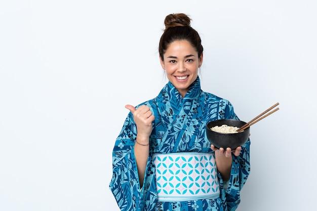 Женщина в кимоно на изолированной белой стене, указывая на сторону, чтобы представить продукт, держа миску лапши с палочками для еды