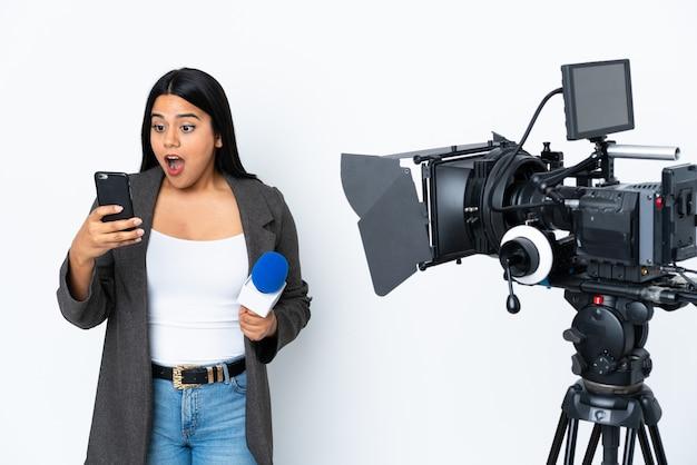 Репортер колумбийской женщины, держащей микрофон и сообщающей новости на белом