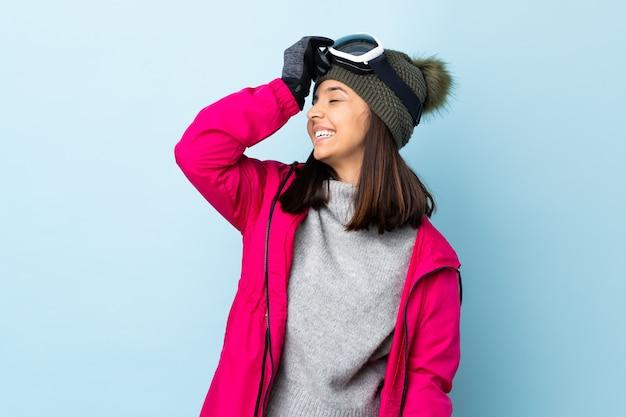 Смешанная девушка-лыжница в сноуборд-очках над синей стеной что-то поняла и решила найти решение