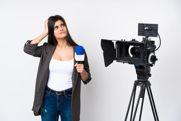 マイクを持って、疑問を抱えて、混乱した表情で白い壁にニュースを報告するレポーター女性