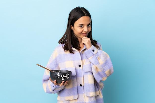 Молодая брюнетка смешанной расы женщина держит миску с лапшой над голубой стене мышления