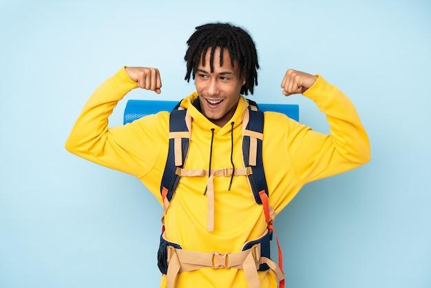 Молодой альпинист афроамериканец человек с большим рюкзаком на синей стене празднует победу