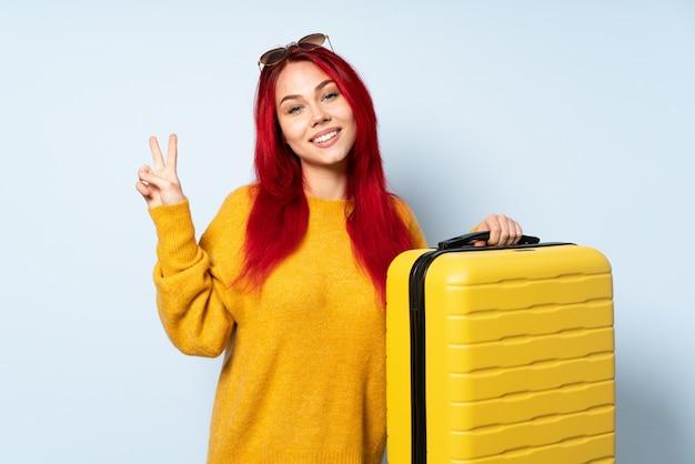 Девушка путешественника держа чемодан на голубой стене усмехаясь и показывая знак победы