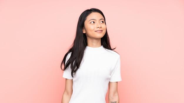 Китайская женщина подростка на розовой стене думая идея пока смотрящ вверх