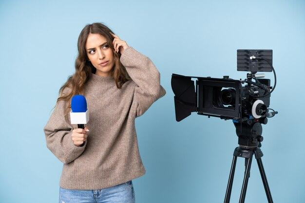 マイクを持っていると疑いがあると混乱の表情でニュースを報告するレポーターの若い女性