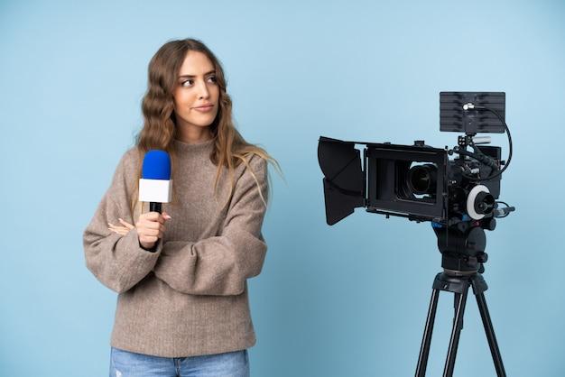 マイクを押しながらアイデアを考えてニュースを報告するレポーターの若い女性