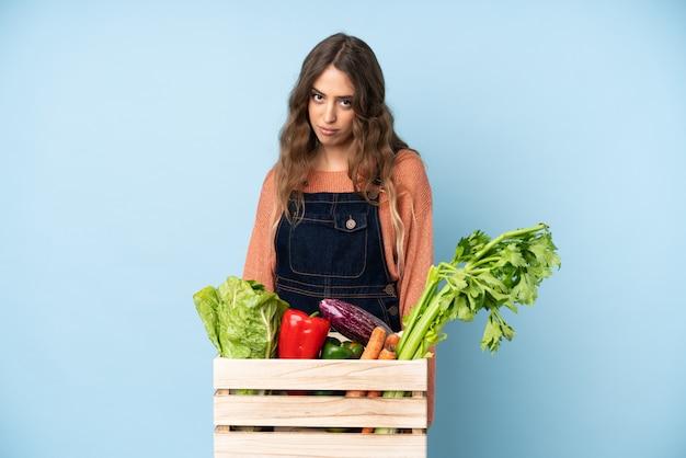 Фермер со свежесобранными овощами в коробке с грустным и подавленным выражением