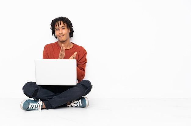 Молодой афроамериканец человек сидит на полу и работает с его ноутбук аплодировал после презентации в конференции