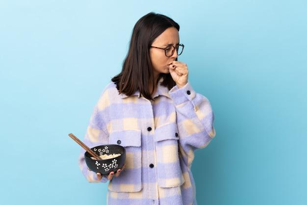 Молодая брюнетка смешанной расы женщина держит миску с лапшой на изолированных синем фоне много кашель