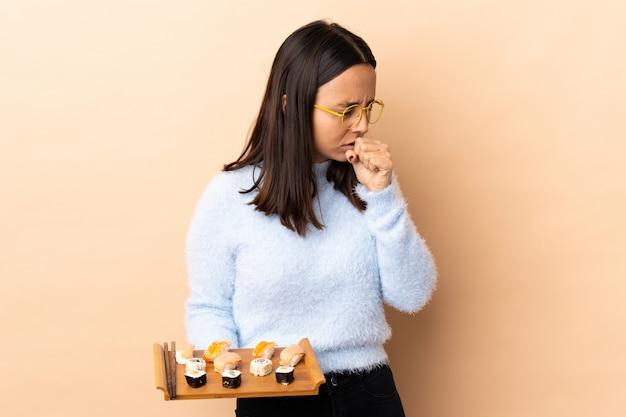 Молодая брюнетка смешанной расы женщина держит суши на изолированных фоне много кашель