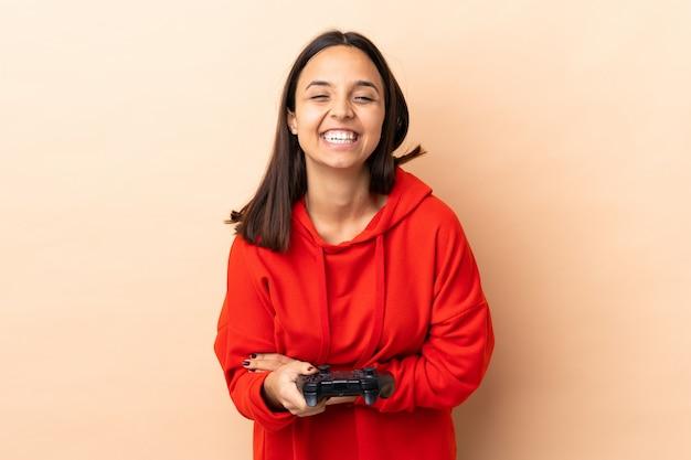 孤立した背景が笑いながらビデオゲームコントローラーで遊ぶ若いブルネットの混血女性