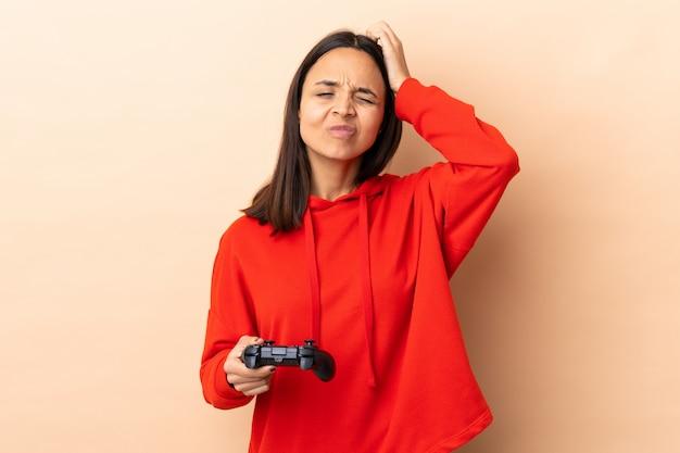 若いブルネットの混血の女性が疑わしい孤立した背景の上でビデオゲームコントローラーで遊んで、顔の表情を混乱させる