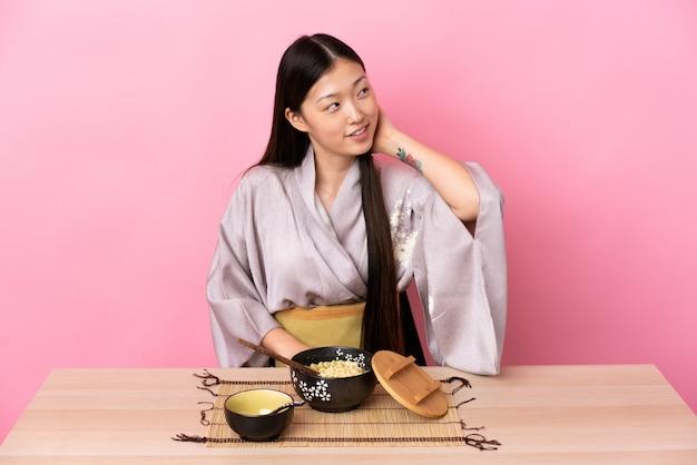 Молодая китайская женщина носить кимоно и есть лапшу, думая идею