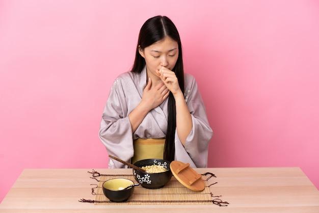 Молодая китайская женщина в кимоно и ест лапшу, много кашляя