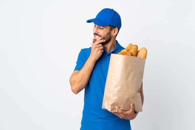 アイデアを考えて側を見て白い壁に分離されたパンの完全な袋を保持している配達人